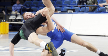 Two collegiate wrestlers, one upended, asics wrestling shoes